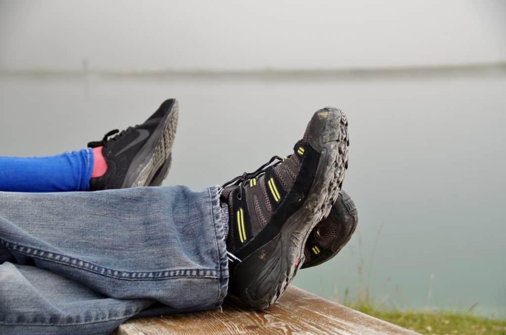 Due paia di piedi accavallati con scarpe sportive infangate poggiano su una panchina all'aperto.