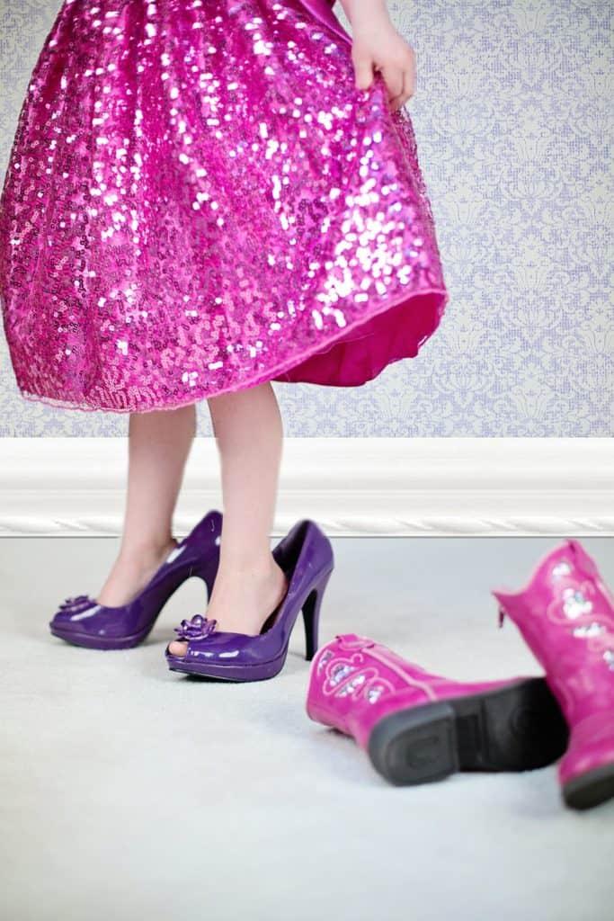 Gambette di bambina con gonna rosa a lustrini e scarpe col tacco viola fuori misura.