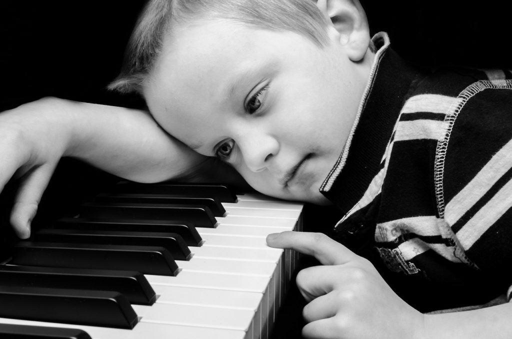 Bambino con il capo appoggiato sulla tastiera di un pianoforte.