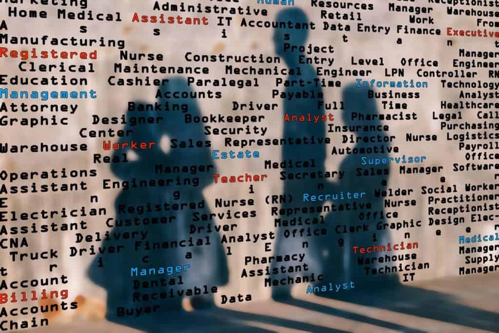 parete dove compaiono parole in inglese scritte nel carattere di programmazione dei computer. Sulla parete vengono proiettate ombre di persone.