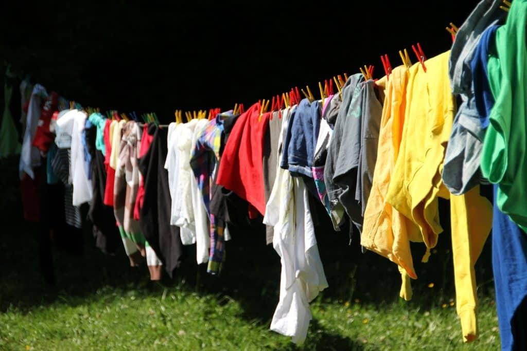 Corda del bucato tesa su un prato, carica di indumenti colorati tenuti sospesi da mollette rosse e gialle