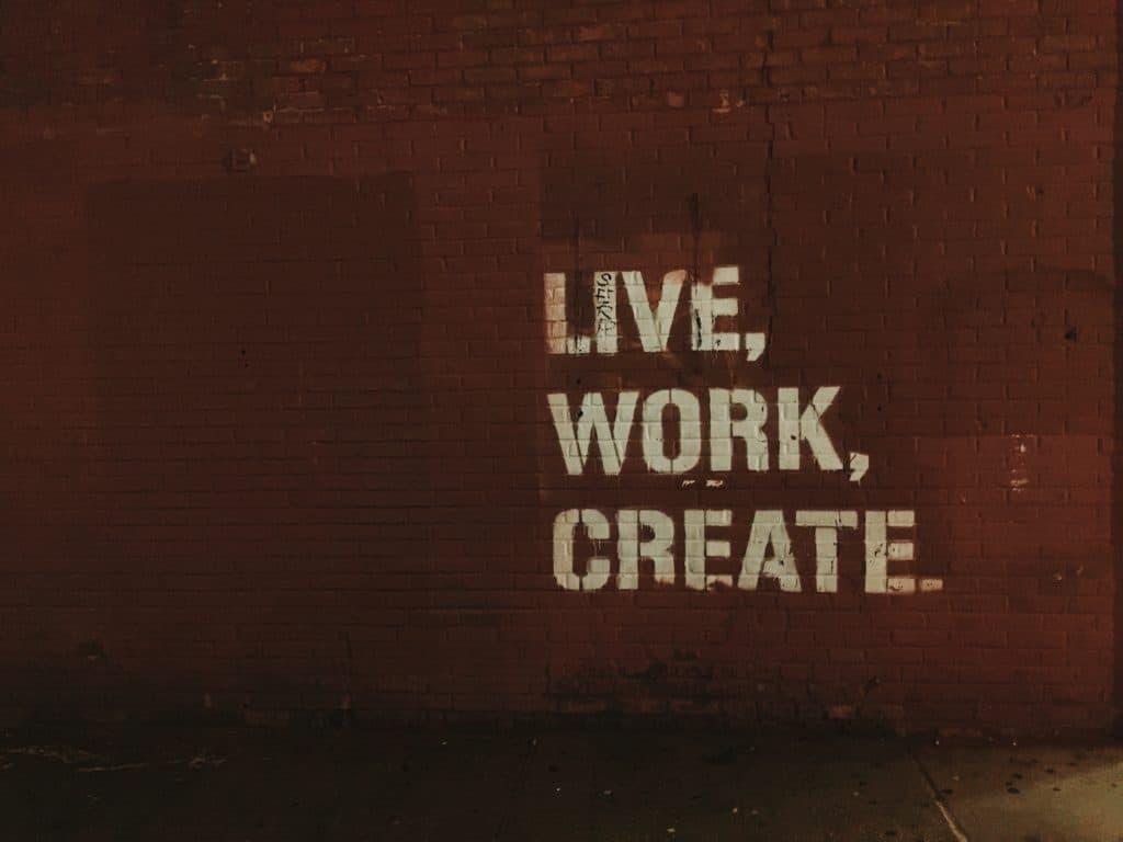 Muro di mattoni rossi con tre parole scritte in colonna: live, work, create. Da tenere presente anche quando sei in pensione.