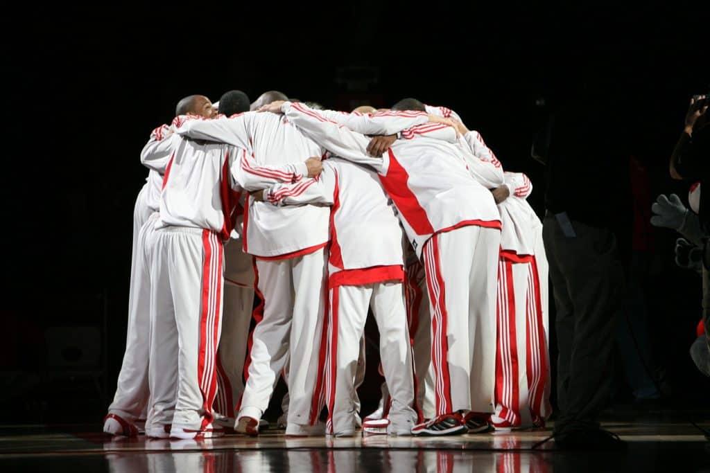 Abito come divisa: atleti in tuta bianca con bande laterali rosse disposti in cerchio fanno il consueto capannello.