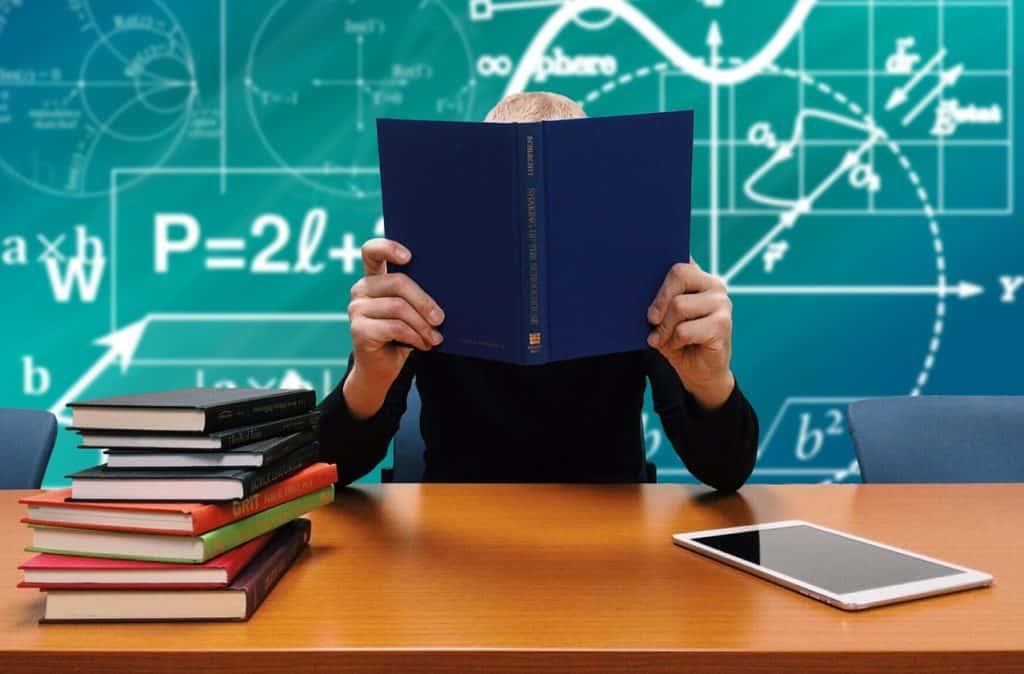 Persona in cattedra davanti a una lavagna coperta di formule matematiche con il viso coperto da un libro con la copertina blu aperto.