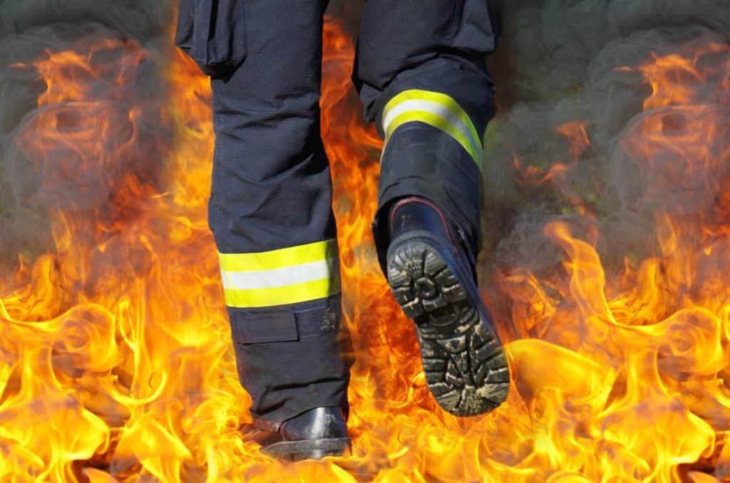 Gambe di pompiere che sta varcando un muro di fuoco: essere triste costringe gli altri a mettersi a rischio per venirti incontro.