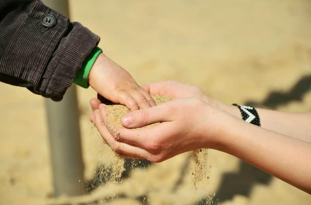 Essere tristi è come essere sempre bambini che vogliono essere accontentati: mano di bimbo che prende la sabbia dalle mani a coppa di una donna.