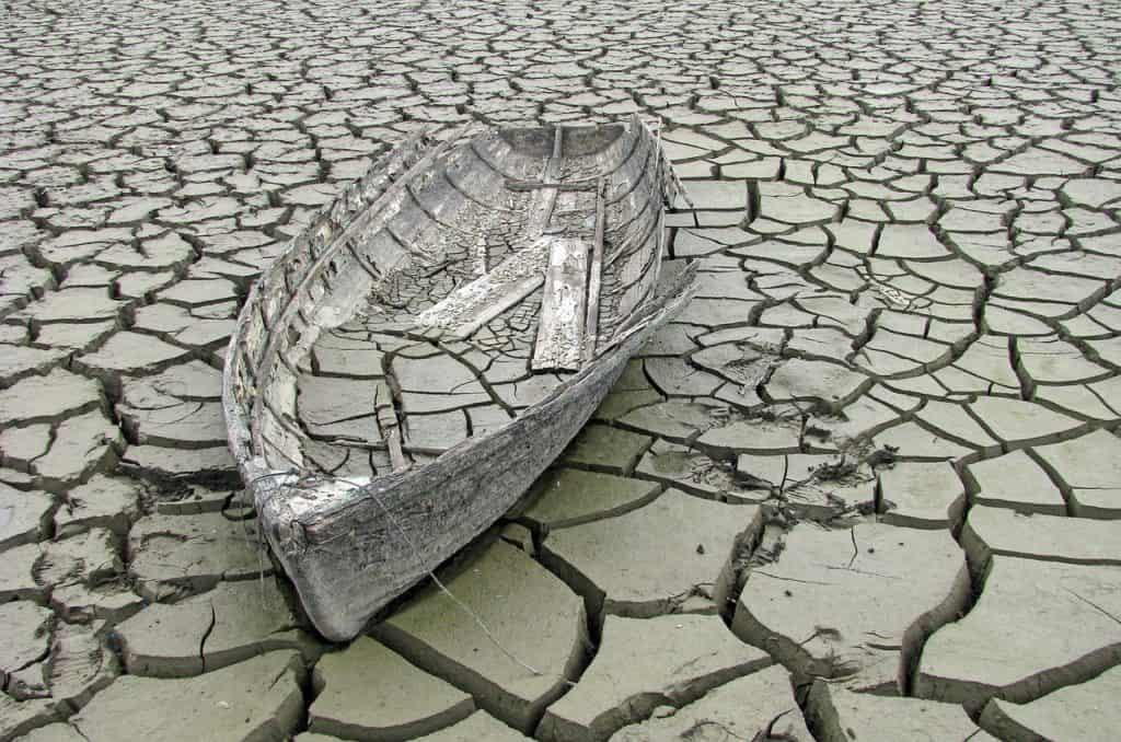 Essere triste inaridisce le persone: una barca abbandonata sul cui fondo giace una crosta di terra crepata. Suolo arido pieno di crepe