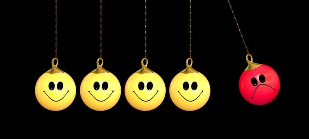 Essere triste danneggia gli altri: quattro ciondoli gialli con smiles sorridenti stanno per essere colpiti da un quinto smile di colore rosso con l'espressione triste.