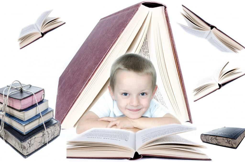 Bambino sui cinque anni, sorridente circondato da libri.