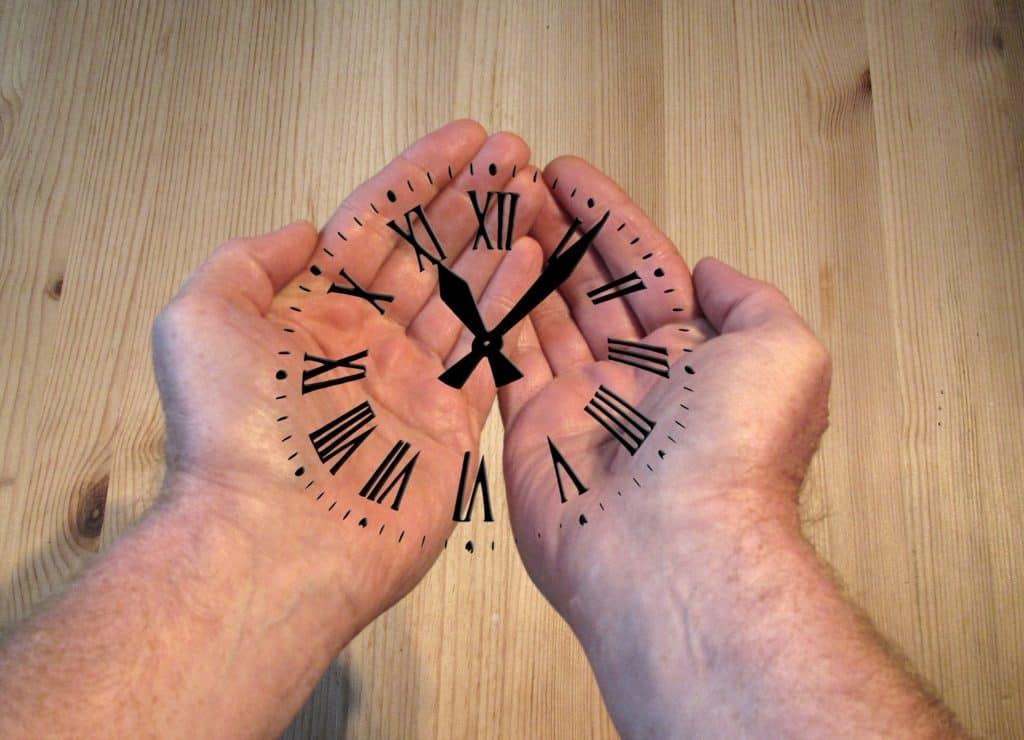 Reagire al momento giusto: mani maschili unite con i palmi verso l'alto e un orologio disegnato sopra.