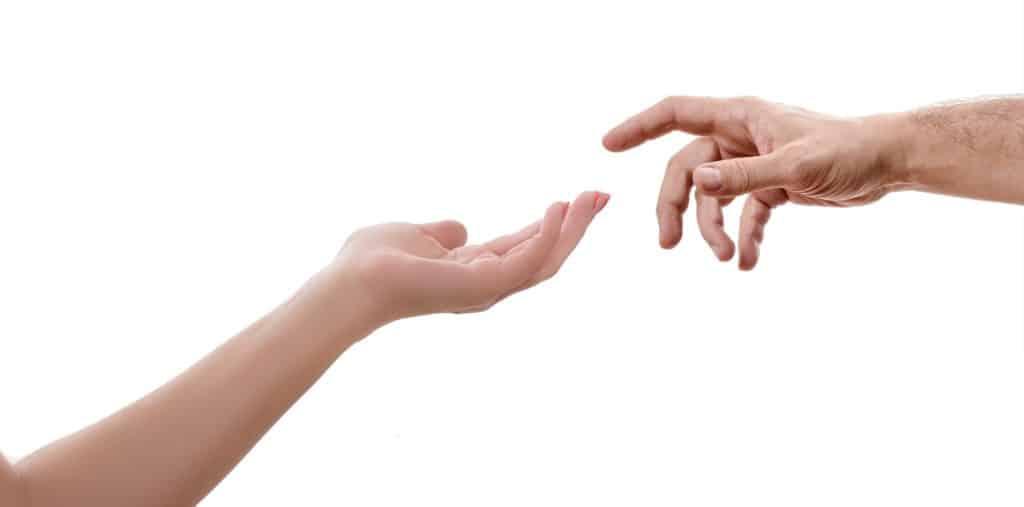 Reagire con compassione: due mani che vanno ad incontrarsi. Citazione dall'affresco dellavolta della Cappella Sistina.