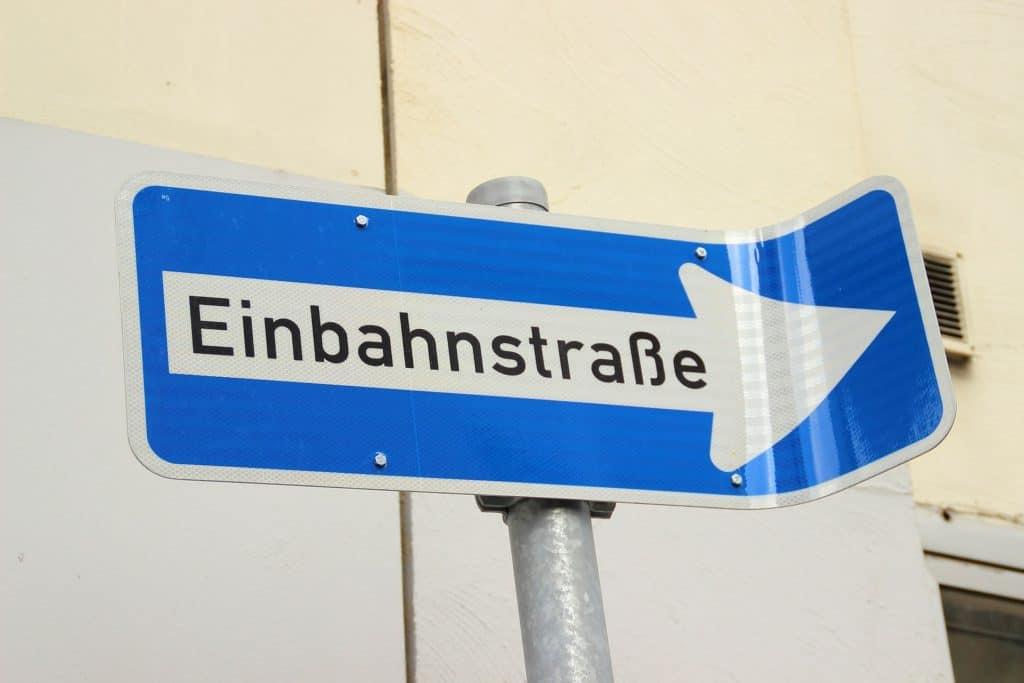 Cartello rettangolare blu curvato  a una sommità con scritta in tedesco: incomprensibile e disorientante.