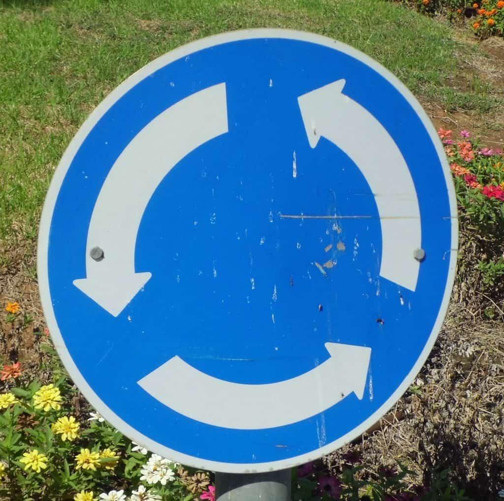 Cartello circolare blu con frecce bianche che indica la circolazione stradale rotatoria.