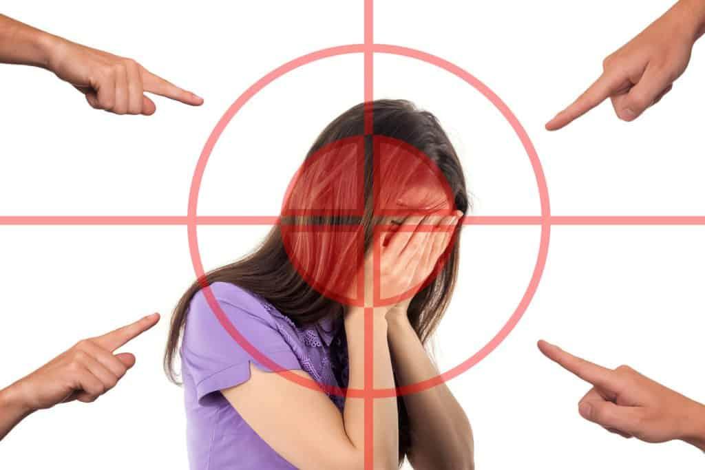 Il dito accusatorio: donna che si copre il volto al centro di un bersaglio con quattro dita puntate contro