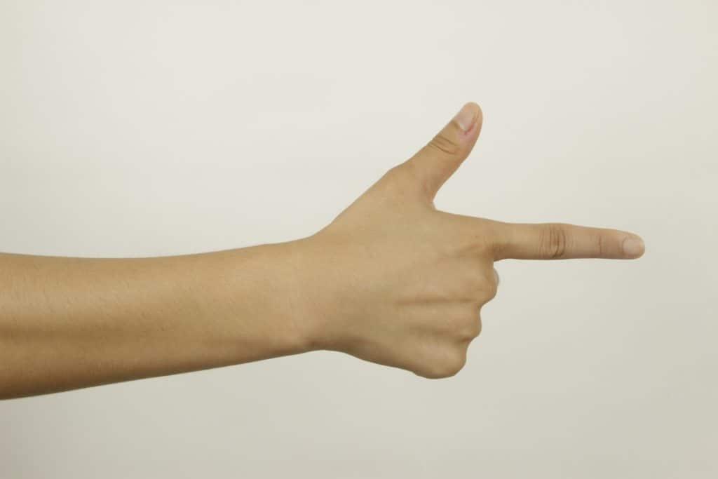Il dito indice  della mano mano con pollice alzato simboleggiano una pistola