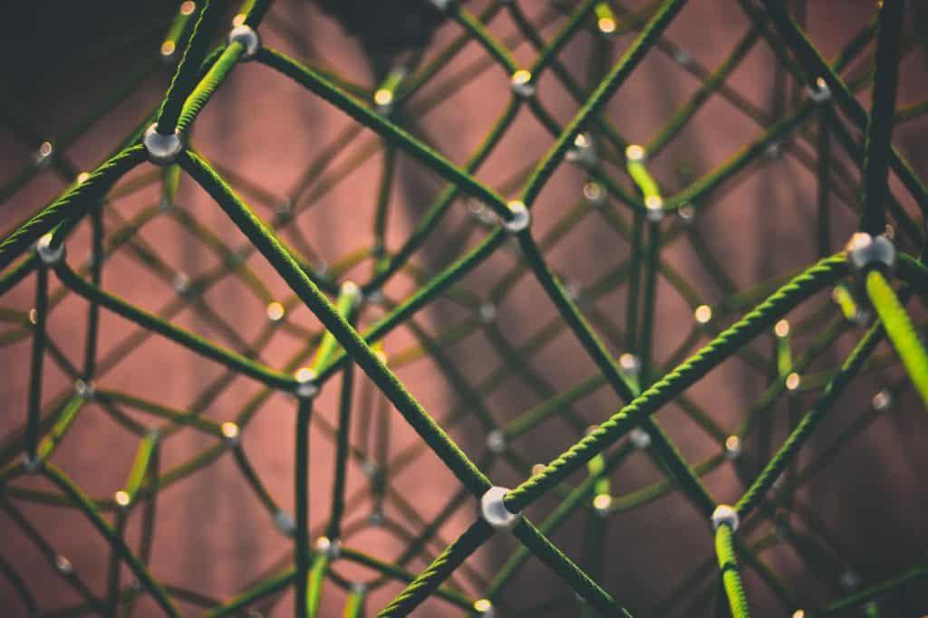 Connessioni: rete di cavi verdi uniti tra loro da snodi di metallo.