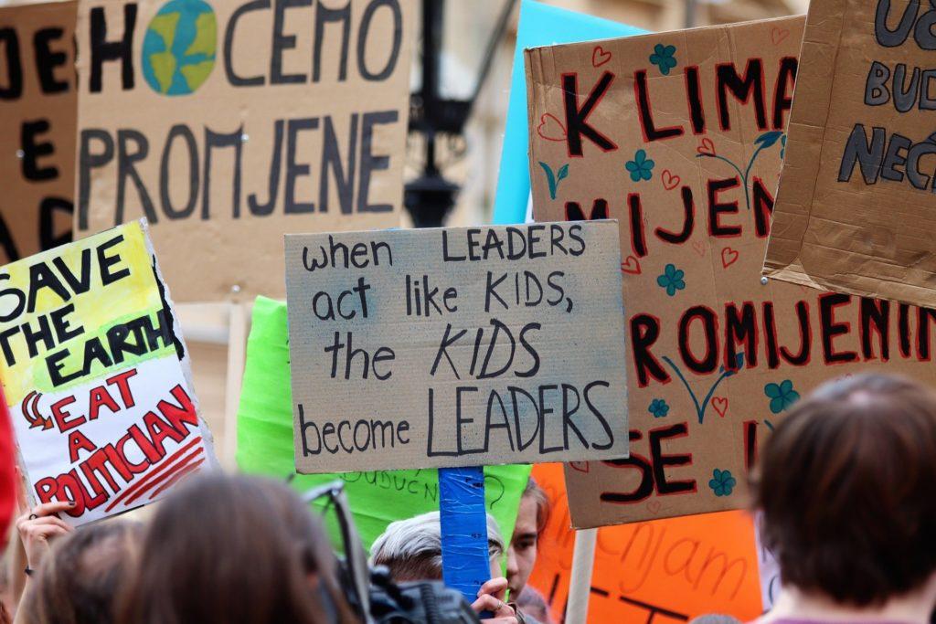 """Cambiare: cartello di protesta in una manifestazione: """"quando i leader si comportano come bambini, i bambini diventano leader""""."""