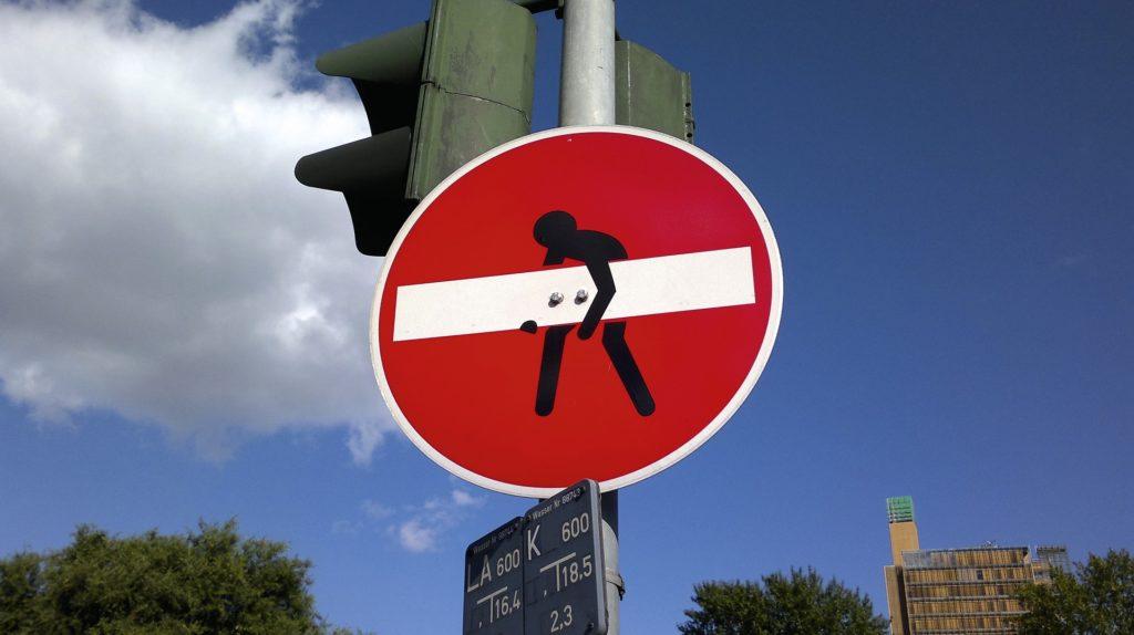 Boomer e la fatica di vivere. Cartello di senso vietato con omino stilizzato che tenta di sollevare il segno bianco su cartello rotondo rosso.