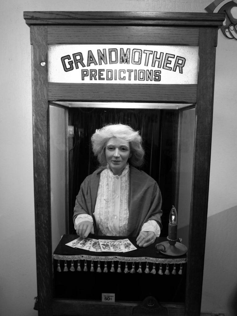 """Automa vestito da lettrice di tarocchi  in abiti ottocenteschi dentro una cabina di legno con la scritta in inglese """"La nonna che predice il futuro""""."""